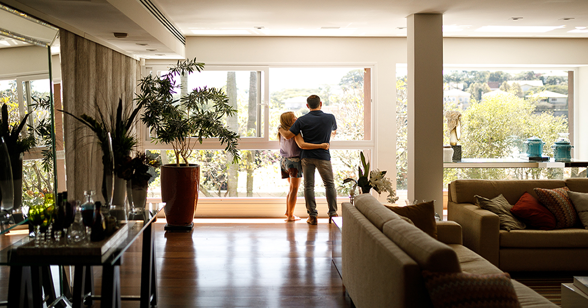 Couple enjoying view from living room window